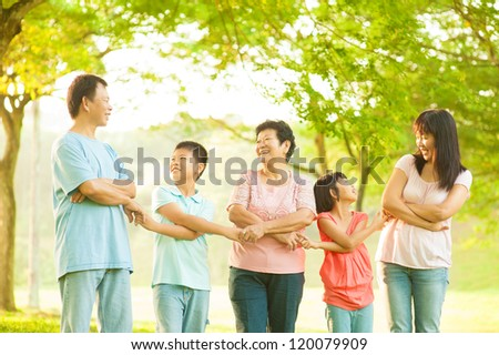 Asian grandparents, parents, grandchildren holding hands at outdoor park - stock photo