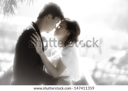 Asian groom and bride embrace - stock photo