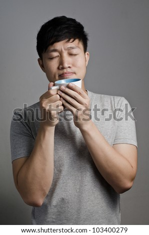 Asian guy hold a cup of coffee