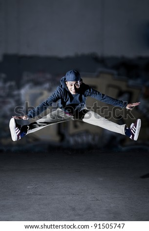 Asian guy jumping in front of a grafitti wall - stock photo