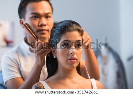 Asian hairdresser doing hairstyle for attractive girl in salon - stock photo