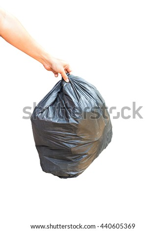 Asian hand carrying garbage bag over pile of garbage bags in a dump - stock photo