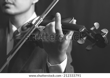 Asian handsome male musician plays violin on dark background, close up and focus to hand / B&W film processed - stock photo