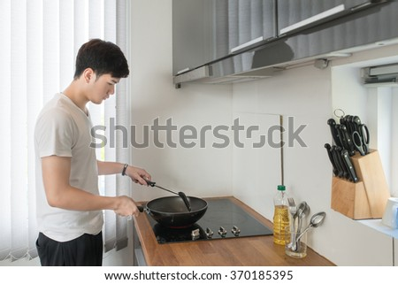 Asian Handsome man cooking in the kitchen at home - stock photo