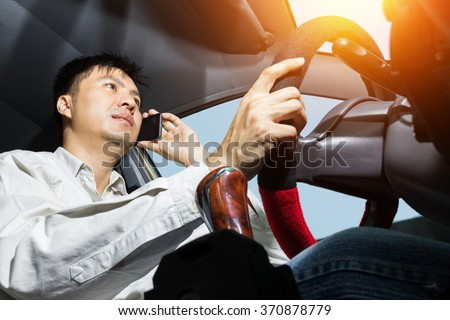 asian handsome man using phone while driving the car - transportation and vehicle concept  - stock photo