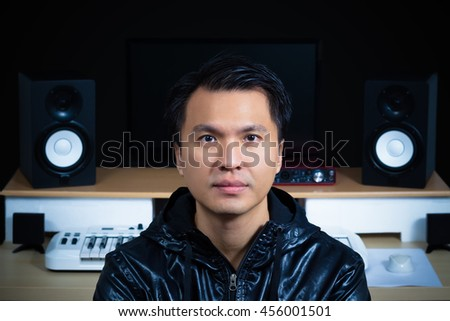 asian handsome music composer, song writer, sound engineer on recording studio background