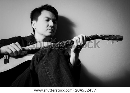 Asian Handsome Musician plays Acoustic Guitar, B&W film processed - stock photo