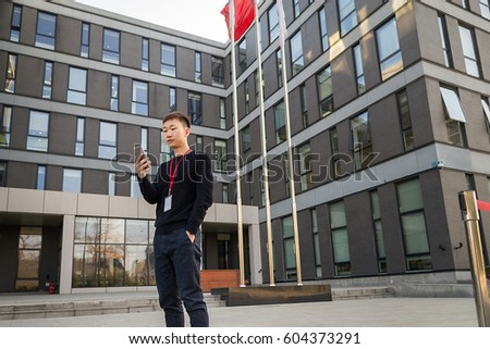 Asian handsome young man with a lanyard standing in front of office buildings using a smart phone and hands in pocket