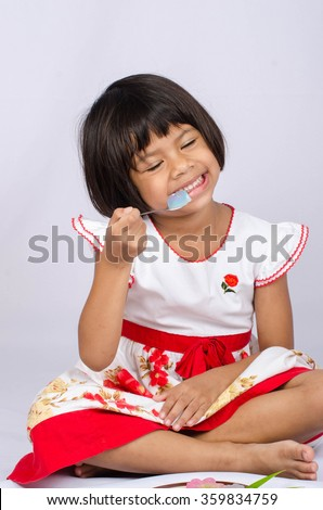 Asian Happy Eating Candy On Grey Background