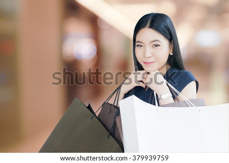 Asian happy shopaholic woman with loads of shopping bags in blurred mall background - stock photo