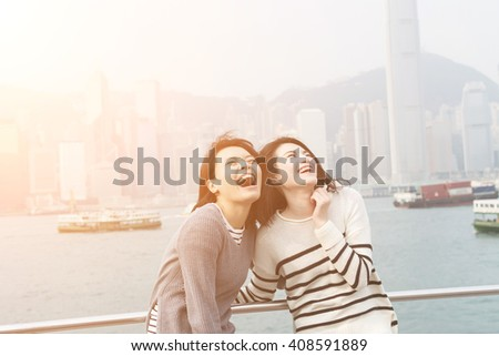 Asian happy young girls traveling at Victoria harbor, Hong Kong, Asia. - stock photo