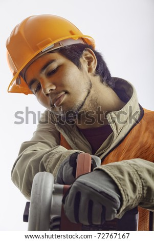 asian hardhat worker with an electric skillsaw - stock photo