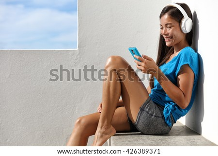 Asian healthy yoga woman listening to smartphone music with headphones relaxing outside on home summer terrace. Active living happy young girl enjoying fitness video or audio program on mobile phone. - stock photo