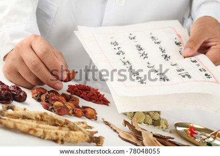 Asian herbalist make a prescription,Chinese characters are names for the herbs. - stock photo