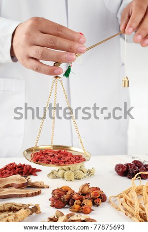 Asian herbalist weighing Chinese medicinal herbs - stock photo