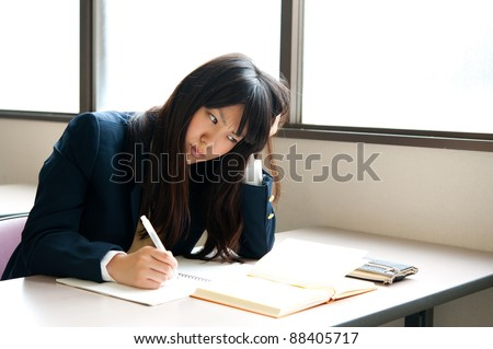 asian high schoolgirl studying in classroom - stock photo