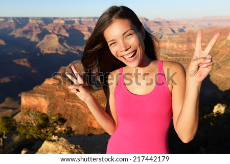 Asian hiker - hiking woman portrait at Grand Canyon. Hiker woman smiling showing victory v hand sign in happy outdoor portrait. Aspirational lifestyle image of female hiker in Arizona, USA. - stock photo