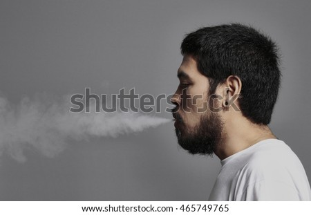 Asian Hipster man smoking electronic cigarette on grey background