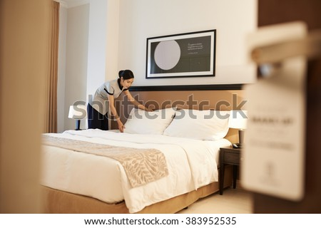 Asian hotel maid making bed, view from the entrance of the room - stock photo