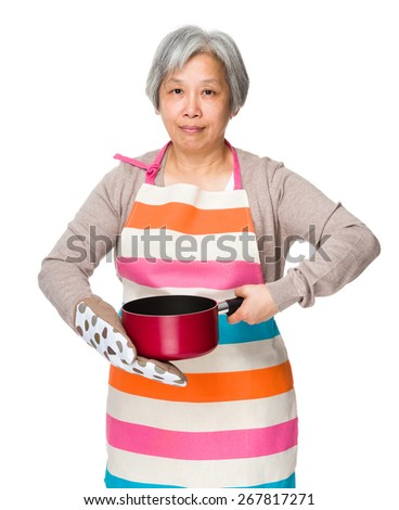 Asian housewife hold saucepan with oven glove  - stock photo