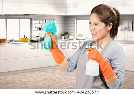 asian housewife holding spray bottle and rag fighting with dirty