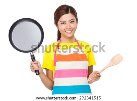 Asian Housewife raised up with frying pan and wooden ladle - stock photo