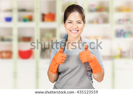 asian housewife wearing rubber gloves thumbs up - stock photo