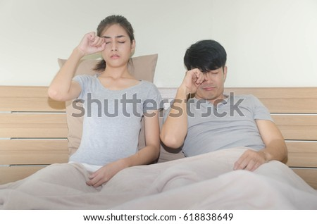 Asian Husband and wife sitting on the bed after  wake up feeling drowsy.