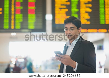 Asian Indian Business man checking on smartphone, doing online web check in at the airport . - stock photo