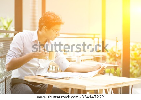 Asian Indian business man reading newspaper while drinking a cup hot milk tea at cafeteria, with beautiful golden sunlight. - stock photo