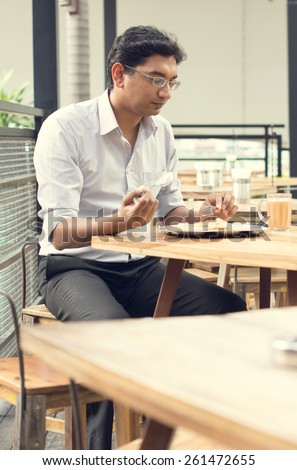 Asian Indian business man reading newspaper while drinking a cup hot milk tea during lunch hour at cafeteria. - stock photo