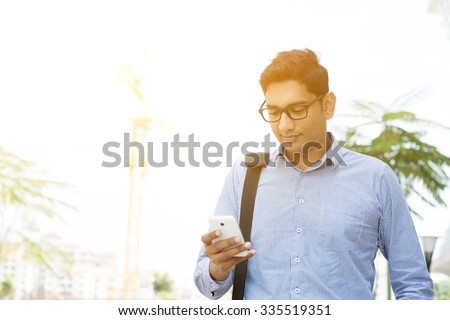 Asian Indian business people texting using smartphone while walking to office, modern urban sunrise view. - stock photo