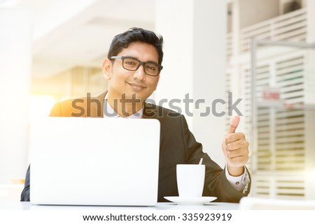 Asian Indian business people using a laptop thumb up at cafe. India male business man, modern building with beautiful golden sunlight as background. - stock photo