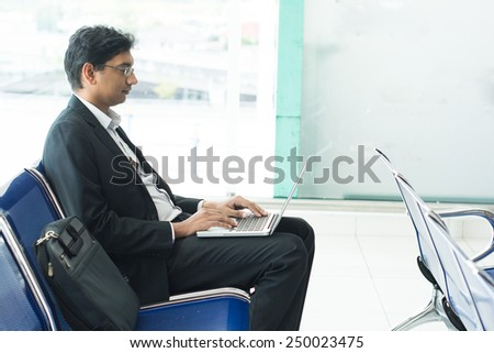 Asian Indian businessman sitting on chair and using laptop while waiting his flight at airport. - stock photo