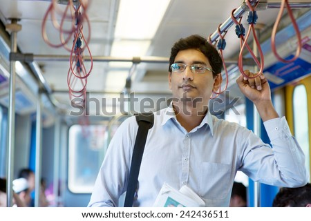 Asian Indian businessman taking ride to work, standing inside train. - stock photo