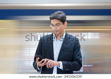 Asian Indian businessman texting using smartphone while waiting train at railway station. - stock photo