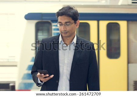 Asian Indian businessman texting using smartphone while waiting train at railway station - stock photo