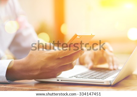 Asian Indian businessman using smartphone and laptop computer at outdoor cafeteria, golden sunset background. - stock photo