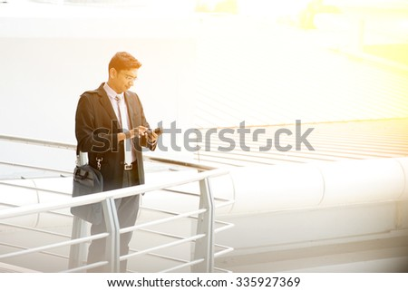 Asian Indian businessman using smartphone, standing at modern office building, skyline at background. - stock photo