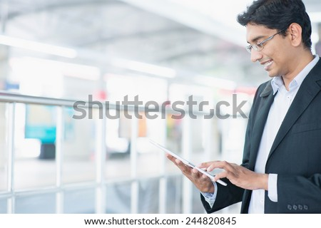 Asian Indian businessman using tablet pc while waiting train at railway station.  - stock photo