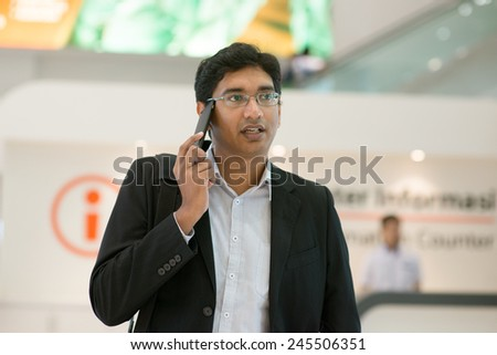 Asian Indian businessman walking by information counter,  talking on phone. - stock photo