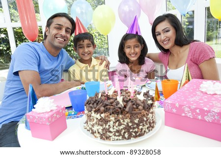 Asian Indian family, mother, father, son & daughter celebrating a birthday party with a chocolate cake - stock photo
