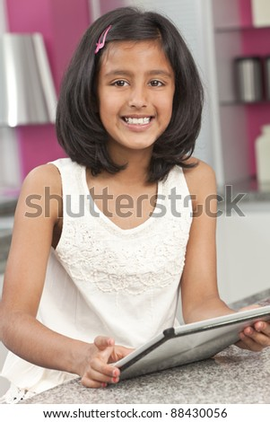 Asian Indian Girl Child Using Tablet Computer at Home - stock photo