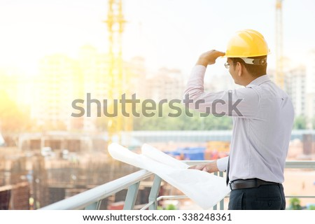 Asian Indian male site contractor engineer with hard hat holding blue print paper looking away inspecting at construction site, crane with golden sunlight at the background.