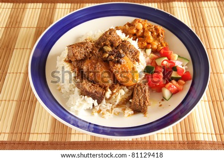 Asian Indian style beef curry on rice with two side dishes - stock photo
