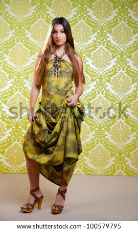 Asian Indian woman with long ethnic dress on green retro wallpaper - stock photo