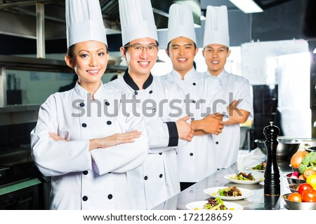 Asian Indonesian and Chinese chefs along with other cooks in restaurant or hotel commercial kitchen cooking, finishing dish or plate - stock photo