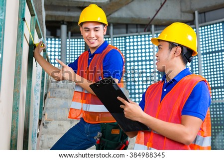 Asian Indonesian builder or craftsman and supervisor with hardhats, checklist and measure tape controlling or checking a wall of a tower building or construction site - stock photo