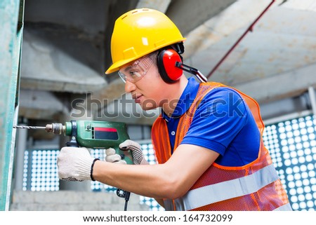 Asian Indonesian builder or worker drilling with a machine or drill, ear protection and hardhat or helmet  in a wall of a tower building or construction site - stock photo