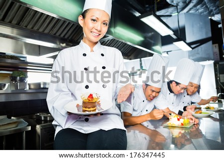 Asian Indonesian chef along with other cooks in restaurant or hotel kitchen cooking, finishing  dish or plate for dessert - stock photo